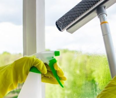 Washing windows. Home cleaning concept. Woman in yellow rubber gloves spray liquid for glasses. Banner format.